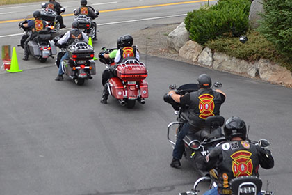 Riders form a line with their motorcycles.
