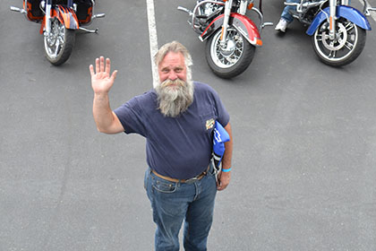 Bearded man in the parking lot, waving to the camera.
