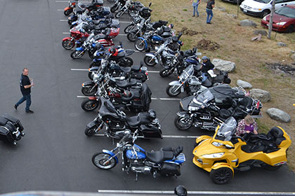 Overview of the parking lot with motorcycles and vehicles.