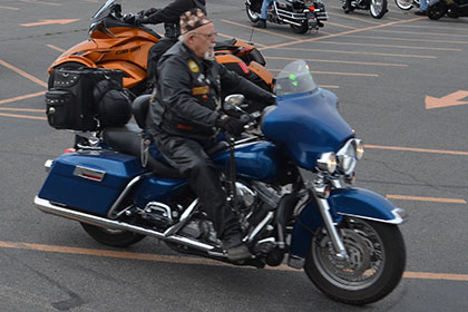 Riders with their motorcycles in the parking lot.