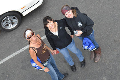 Three women standing in the parking lot.