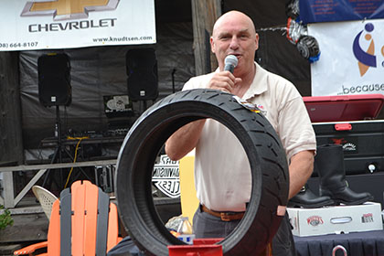 Man on microphone standing behind a motorcycle tire and motorcycle lift.