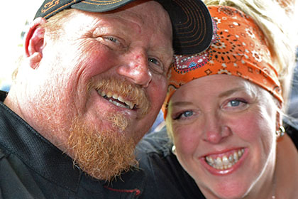 Bearded man with hat and a woman with an orange bandana, smiling for camera.
