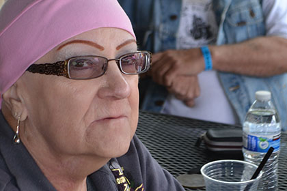 Woman wearing a pink bandana sitting at a table outside with a bearded man.