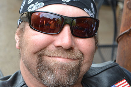 Man wearing sunglasses and bandana smiles for the camera.