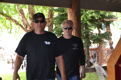 Two guys with dark sunglasses, walking toward the camera.