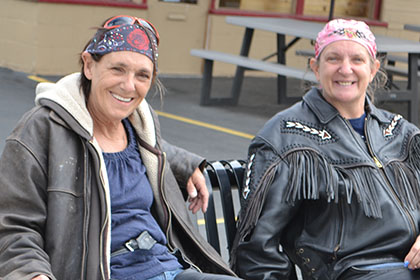 Two people wearing bandana sit on a bench outside.