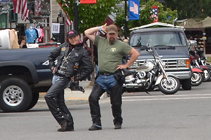 Two people pose for the camera while others gather next to their motorcycles.