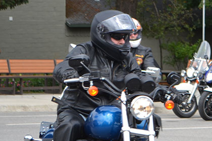 Rider driving their motorcycle while other riders sit on their parked motorcycles.