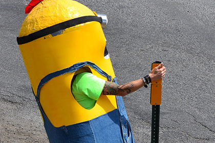 Person dressed as a Minion standing on side of the road.