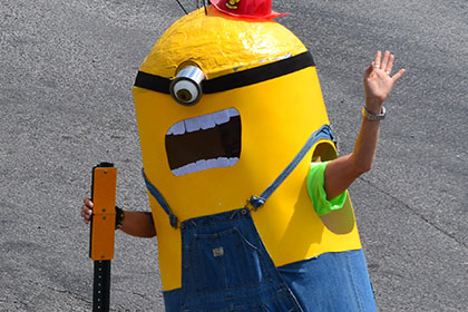 Person dressed as a Minion waves to the camera.