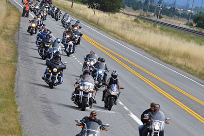 Riders form two long rows while riding on the road.