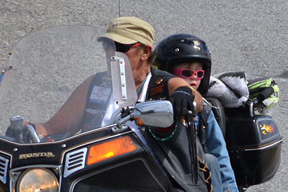 Adult and child on a motorcyle.