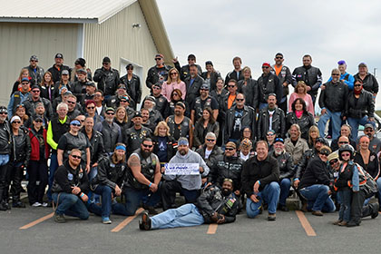 Large group of riders pose for group photo.