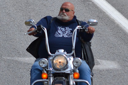 Bearded man riding his motorcyle.